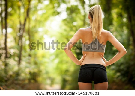 photo of sexy female with tonic bottom looking at running path - stock photo