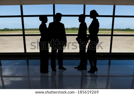 Photo of silhouetted businesspeople standing against airport window - stock photo