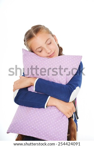 Photo of sleepy school girl holding pillow. Isolated on white background. Concept for sleepiness at school lessons - stock photo