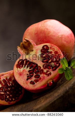 photo of sliced pomegranate in poor art style in front of rural background - stock photo