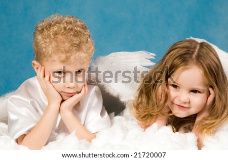 Photo of small boy and girl in angel dresses lying on white cloud and having rest