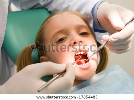 Photo of small girl looking at camera with open mouth while it being examined by dentist - stock photo