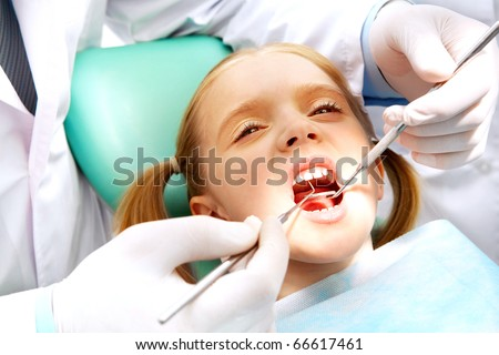 Photo of small girl with open mouth while it being examined by dentist - stock photo