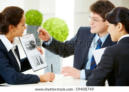 Photo of smart business team discussing documents in the office - stock photo