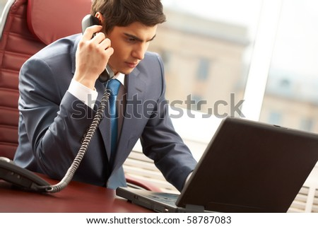 Photo of smart businessman calling somebody before laptop in office - stock photo