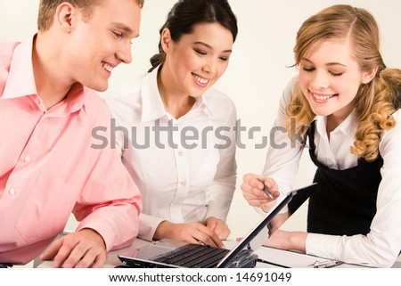 Photo of smart professional pointing at laptop screen while two colleagues looking at it with smiles