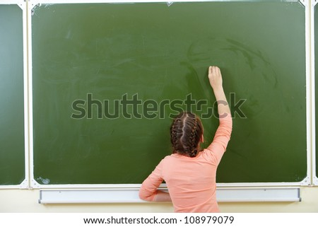 Photo of smart pupil going to write something on blackboard