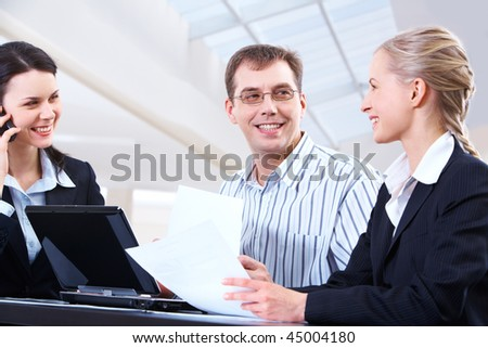 Photo of smart woman holding paper in hand with two colleagues looking at her with smiles