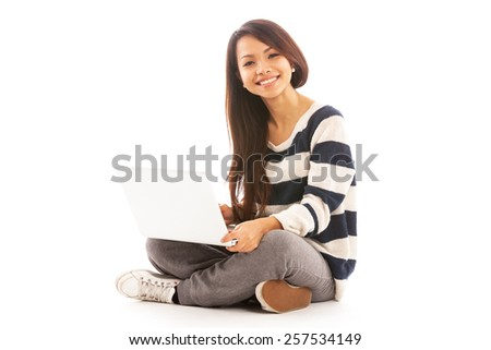 Photo of smiling asian girl sitting with notebook over white isolated background - stock photo