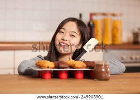 photo of smiling asian woman in the kitchen with tray full of muffins - stock photo