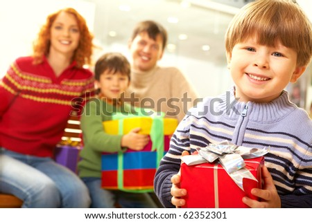 Photo of smiling boy holding present on background of his family