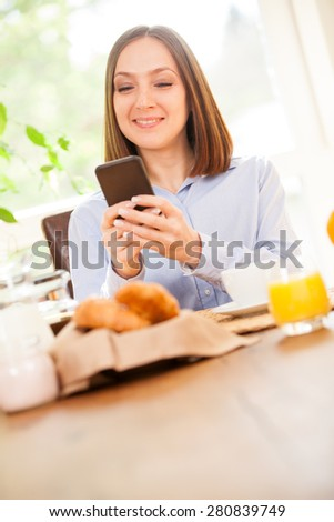 Photo of smiling brunette businesswoman having breakfast while checking her emails - stock photo