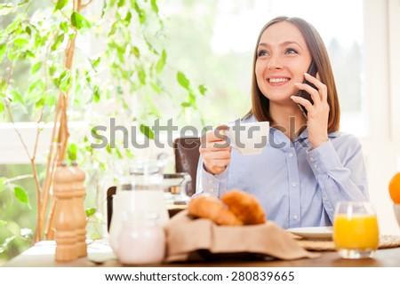 Photo of smiling brunette businesswoman phoning while having breakfast - stock photo