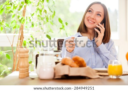 Photo of smiling brunette businesswoman phoning while having breakfast