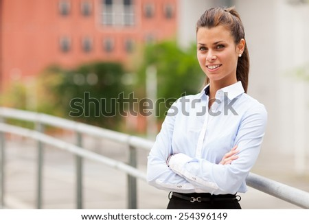 Photo of smiling caucasian businesswoman standing outdoor smiling towards the camera - stock photo