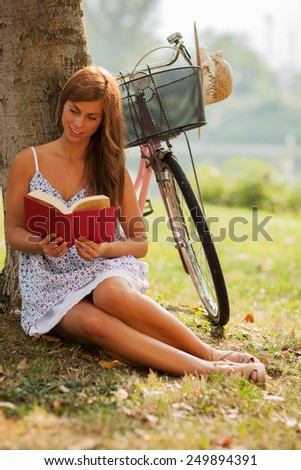 photo of smiling caucasian woman reading a book next to a tree where her bike is standing - stock photo