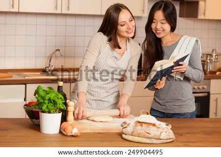 photo of smiling caucasian woman working on a dough while her friend is reading a cookbook