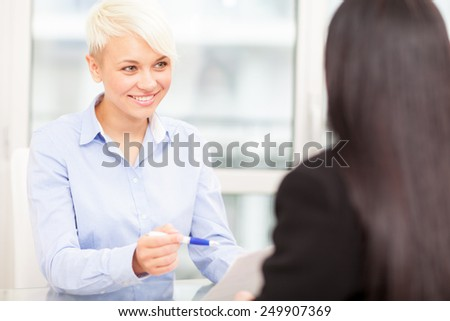photo of smiling female manager doing a job interview - stock photo