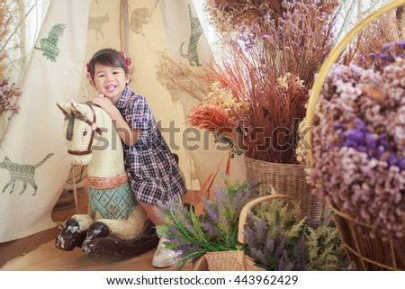 Photo of smiling little girl on a horse. - stock photo