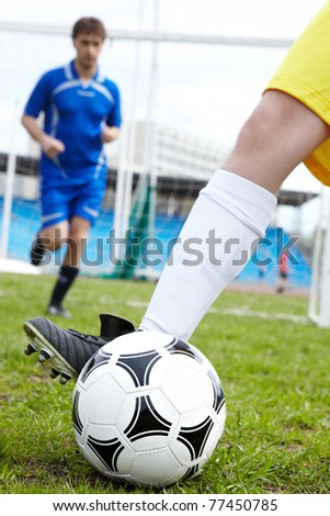 Photo of soccer ball being kicked by footballer during game - stock photo