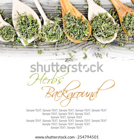 Photo of spoons dried herb leaves on wooden board with white space for text - stock photo
