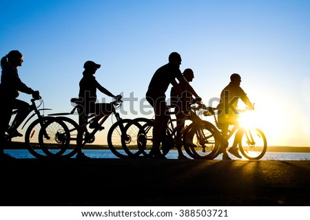Photo of sporty company friends on bicycles outdoors against sunset. - stock photo