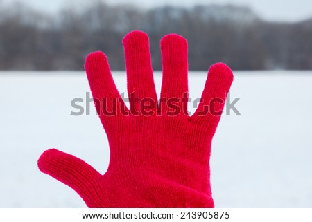 photo of spread out hand in red woolen glove on winter background in nature, concept of joy in winter time - stock photo