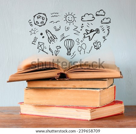 photo of stack of old books. top book is open with set of infographics. imagination and education concept. - stock photo