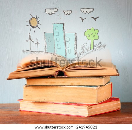 photo of stack of old books. top book is open with set of infographics. imagination and education concept - stock photo