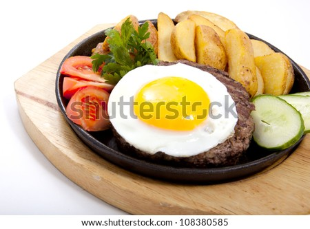 Photo of steak with potatoes and egg in a frying pan - stock photo
