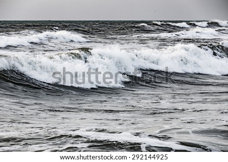 Photo of storming sea with high and small waves with splashes and foam. The sky is gray, smooth and cloudless. - stock photo