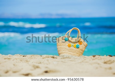 Photo of straw beach bag with flowers on exotic white sand beach - stock photo