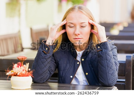 Photo of stressful young woman with headache - stock photo