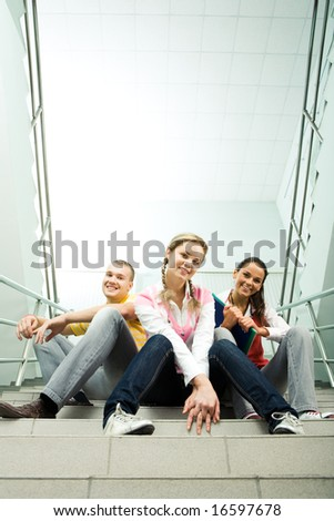 Photo of students in casual clothing looking at camera in the corridor - stock photo