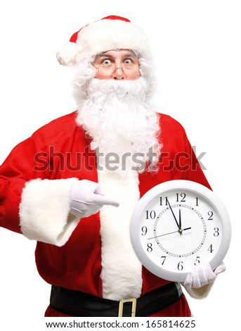 Photo of stunned Santa holding clock showing five minutes to midnight  - stock photo