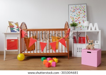 Photo of stylish room for babygirl with wooden crib - stock photo
