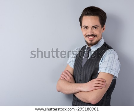 Photo of stylish young businessman wearing striped suit. He smiling and looking at camera