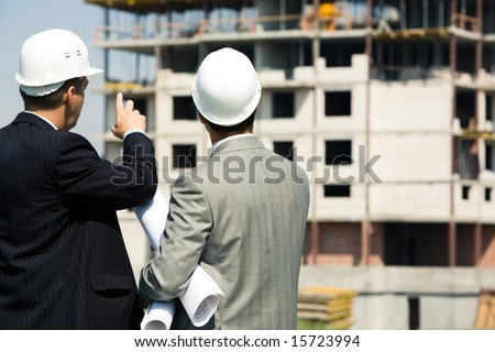 Photo of successful architect pointing to the building with foreman near by - stock photo
