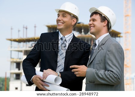 Photo of successful architect with foreman near by on construction site - stock photo