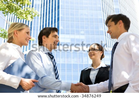 Photo of successful associates handshaking after striking deal outdoors at meeting - stock photo