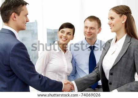 Photo of successful associates handshaking after striking deal with partners near by - stock photo