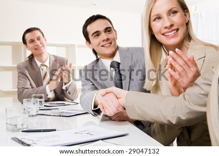Photo of successful business partners handshaking after striking deal while their colleagues applauding - stock photo