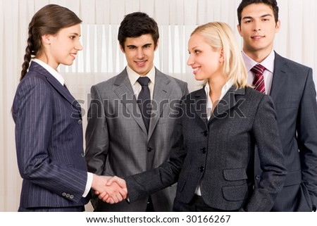 Photo of successful business partners handshaking after striking deal while their colleagues near by - stock photo