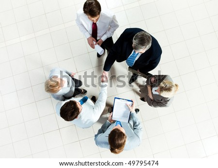 Photo of successful business partners handshaking after striking deal with some employees near by