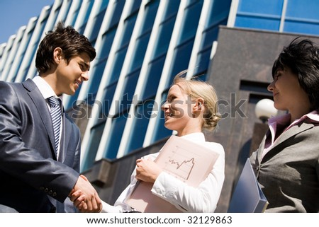 Photo of successful business partners handshaking after striking deal with their colleague near by - stock photo