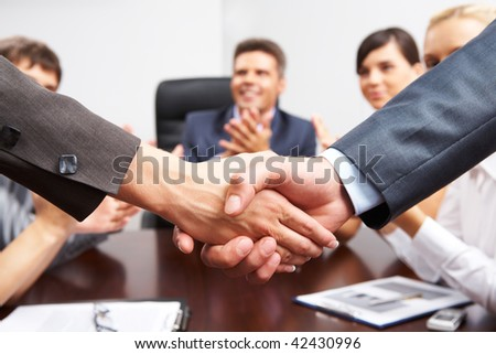 Photo of successful business partners handshaking after striking great deal with applauding people at background - stock photo