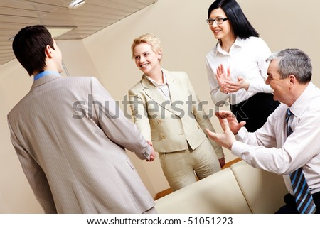 Photo of successful business partners handshaking after striking great deal with applauding people near by - stock photo