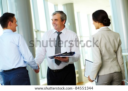 Photo of successful business partners handshaking after striking great deal with young colleague near by - stock photo