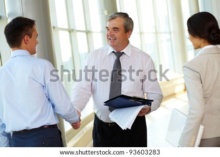 Photo of successful business partners handshaking after striking great deal with young colleague near by