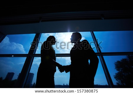 Photo of successful businessman and businesswoman handshaking after striking deal